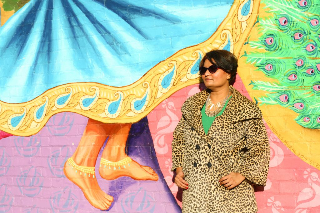 Photo of a woman named Manasi wearing an animal print coat standing in front of a wall with bright colored graffiti that depicts an Indian woman dancing and peacock feathers